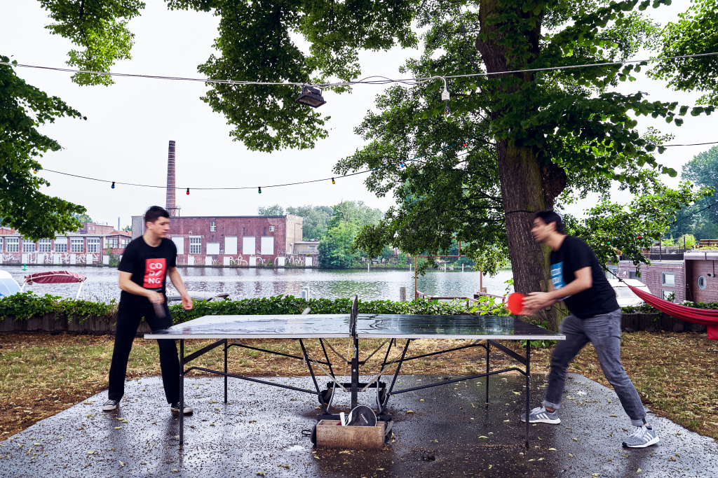 Two students playing table tennis in the backyard of the WBS Coding Campus in Berlin.