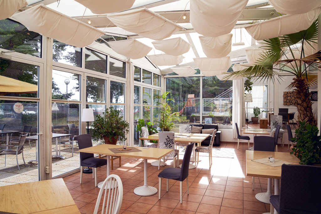 Dining tables in the Berlin campus' conservatory.