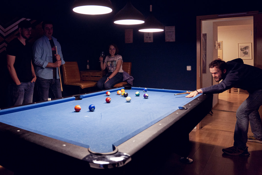 Four students playing pool at the Berlin campus of WBS CODING SCHOOL.