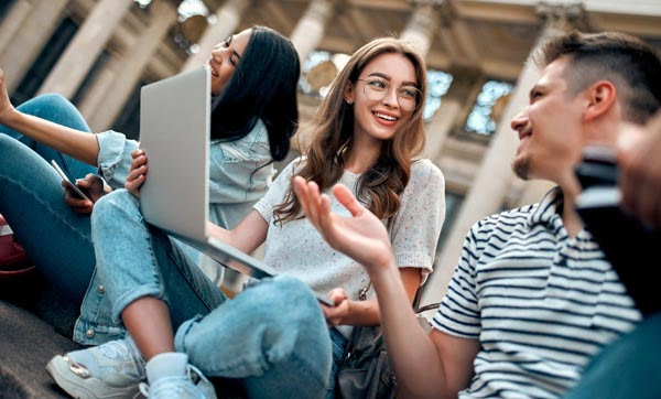 group of students sitting outside with laptop
