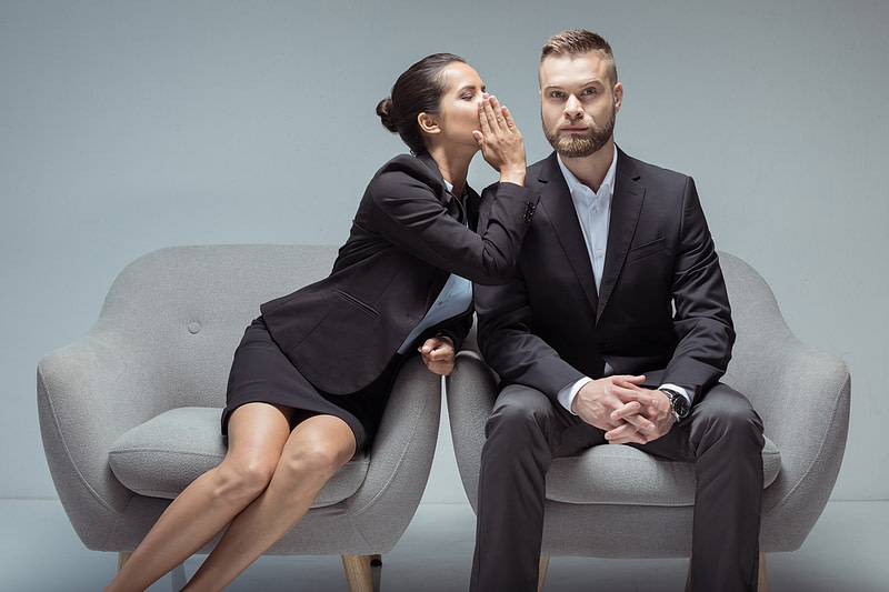 businesswoman whispering something on colleague's ear while sitting on chairs