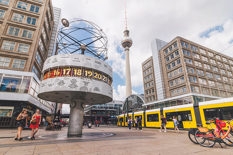 World time clock at Berlin Alexanderplatz with TV tower in the background.