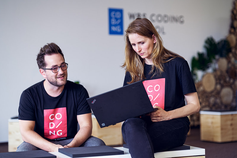 Erika and Tim sitting in the WBS CODING SCHOOL's classroom in Berlin looking at a laptop.