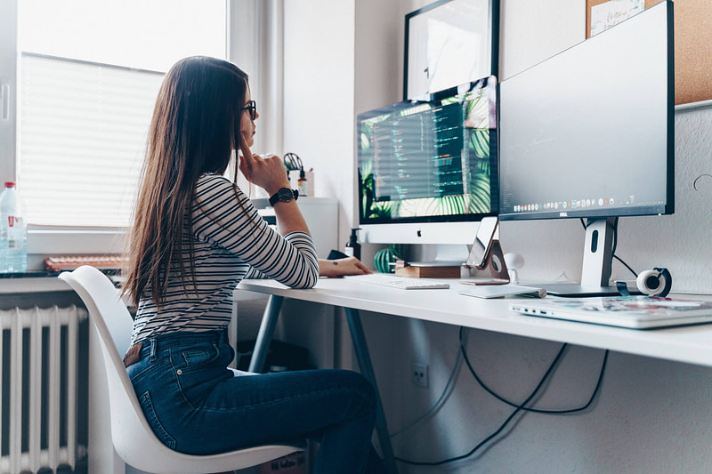 Young woman sitting at her desk in front of two screens learning how to code to become a web developer.
