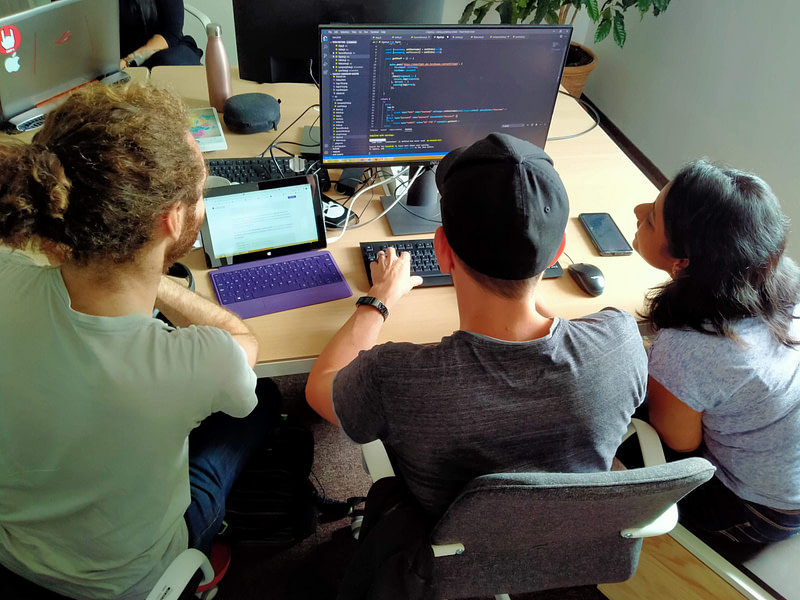 Three students of WBS CODING SCHOOL working on their coding project