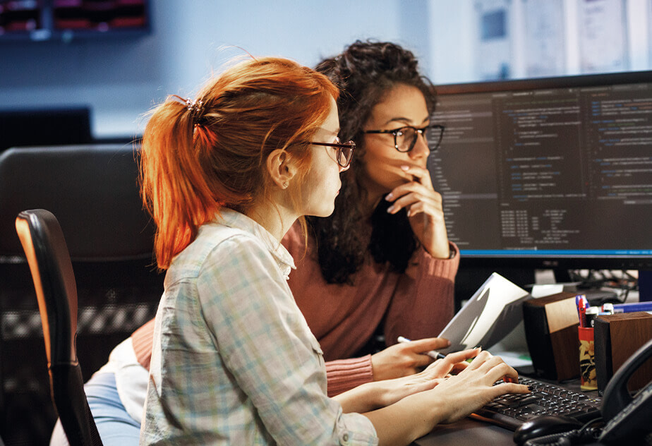 Two young women coding during a web development bootcamp