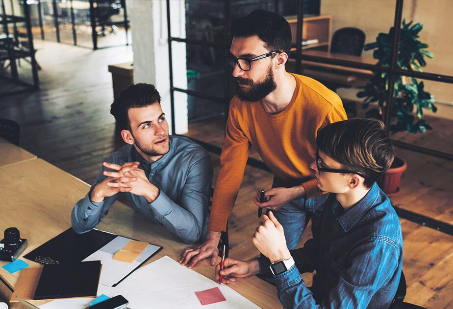 Drei Männer sprechen über ihr Softwareprojekt.